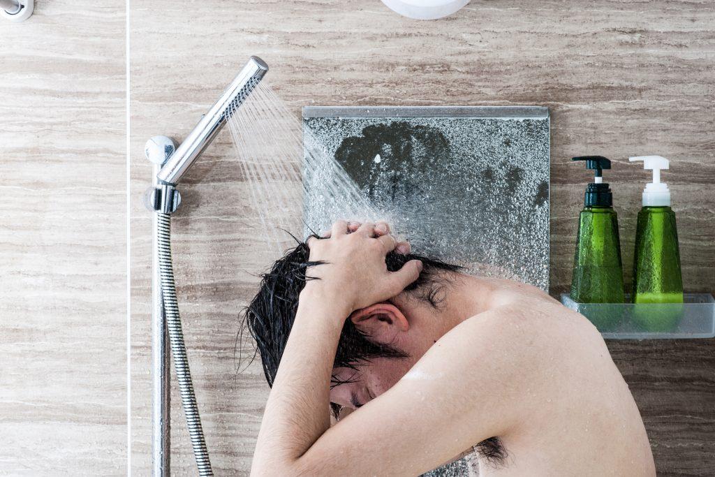 シャワーを浴びる男性